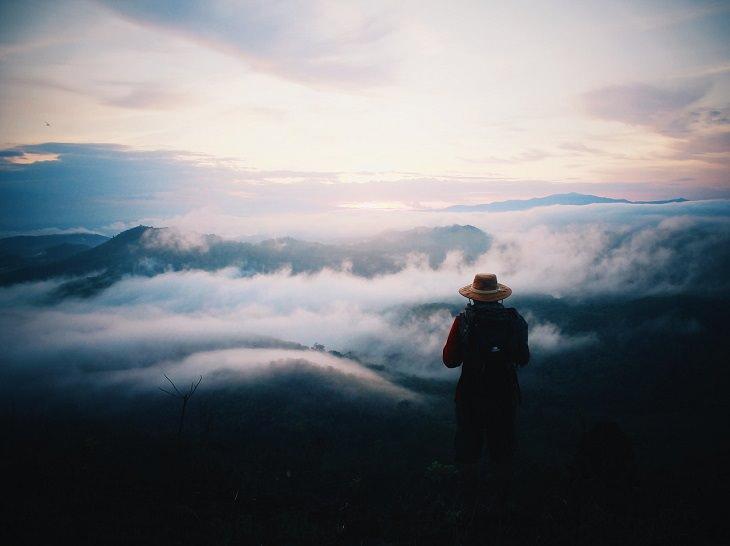 סרטי המסעות המומלצים ביותר: אדם עומד על הר שמולו שמש ועננים