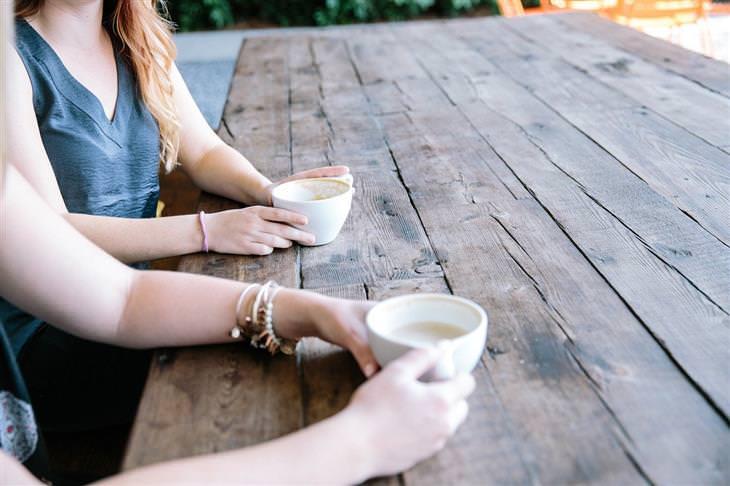 איך להקשיב לאחרים: נשים יושבות מול שולחן עם כוס קפה