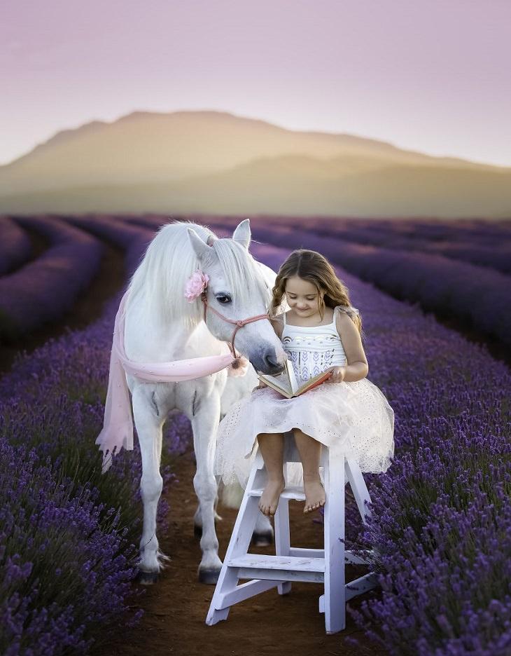 בעלי חיים על רקע שדה סגול: ילדה מקריאה ספר לסוס בשדה