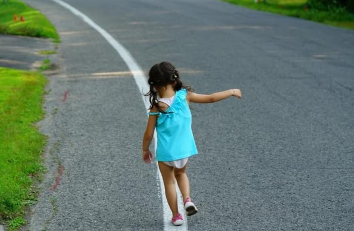 עצות להורים שצריכים להשאיר ילד לבד בבית: ילדה משחקת על כביש