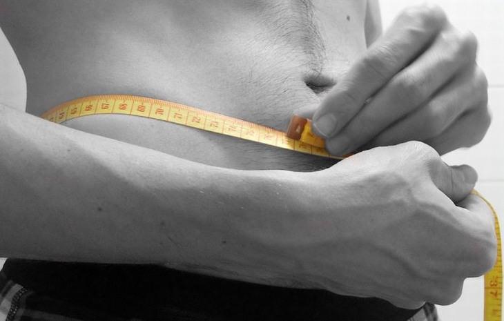 איך להוריד שומן בבטן: גבר מודד את היקף הבטן שלו
