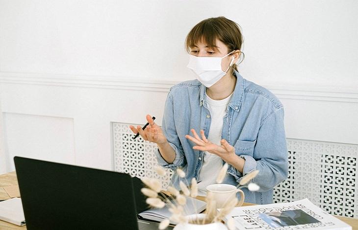דיני עבודה בתקופת הקורונה: אישה עובדת עם מסכת פנים