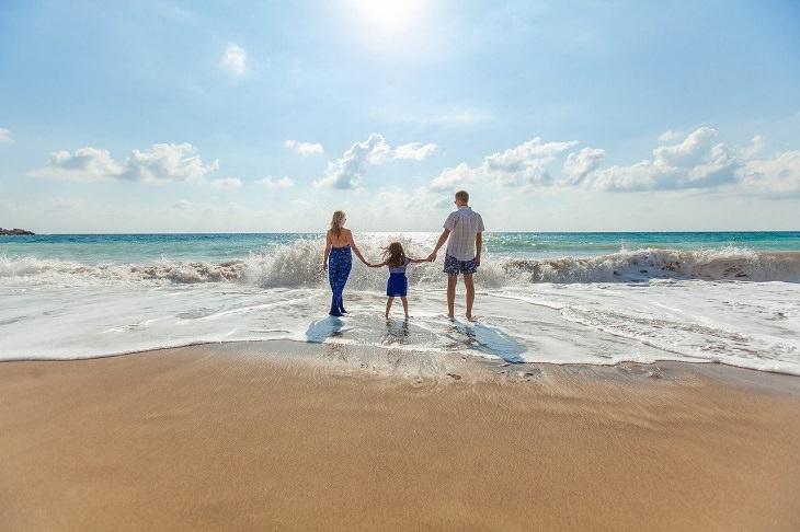 פיתוח חוסן נפשי אצל ילדים: זוג הורים וילדתם על שפת הים מול הגלים