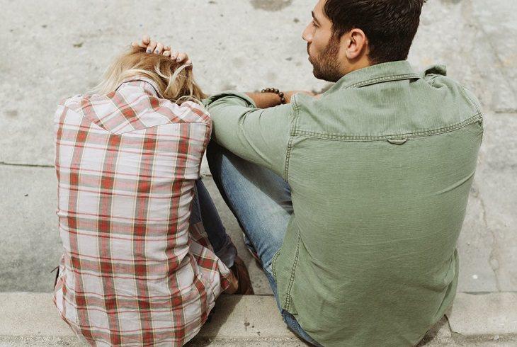 סדקים בזוגיות ודרכים לתיקונם: זוג יושב על המדרכה, כשהבחורה מחזיקה את ראשה