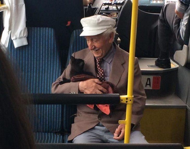 חיות מחמד מביטות על בעליהם באהבה: איש מבוגר מחזיק חתול באוטובוס