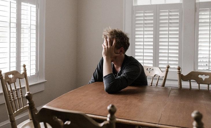 איך להילחם בשנאה עצמית: גבר מתוסכל יושב ליד שולחן