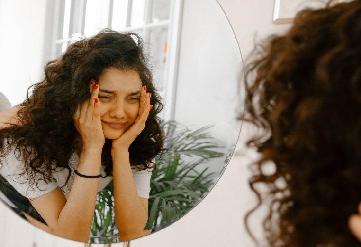 איך להילחם בשנאה עצמית: אישה מביטה במראה ובוכה
