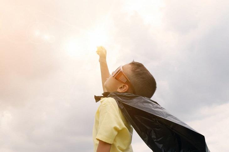 תפקודים ניהוליים אצל ילדים: ילד עם גלימה מסתכל מעלה ומרים את ידו כמו סופרמן