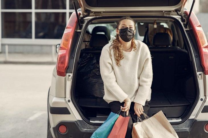 שינויים בתרבות הצריכה בעקבות נגיף הקורונה: בחורה עם מסכה, יושבת ליד מכונית ומחזיקה שקיות