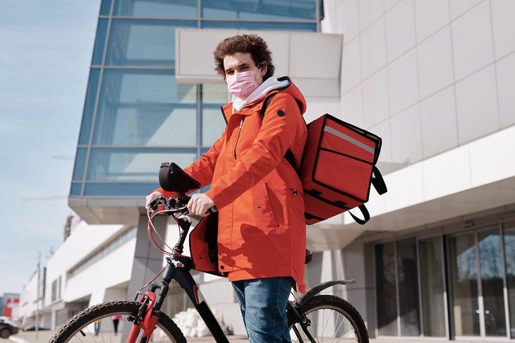 שינויים בתרבות הצריכה בעקבות נגיף הקורונה: שליח אוכל עומד ליד אופניים