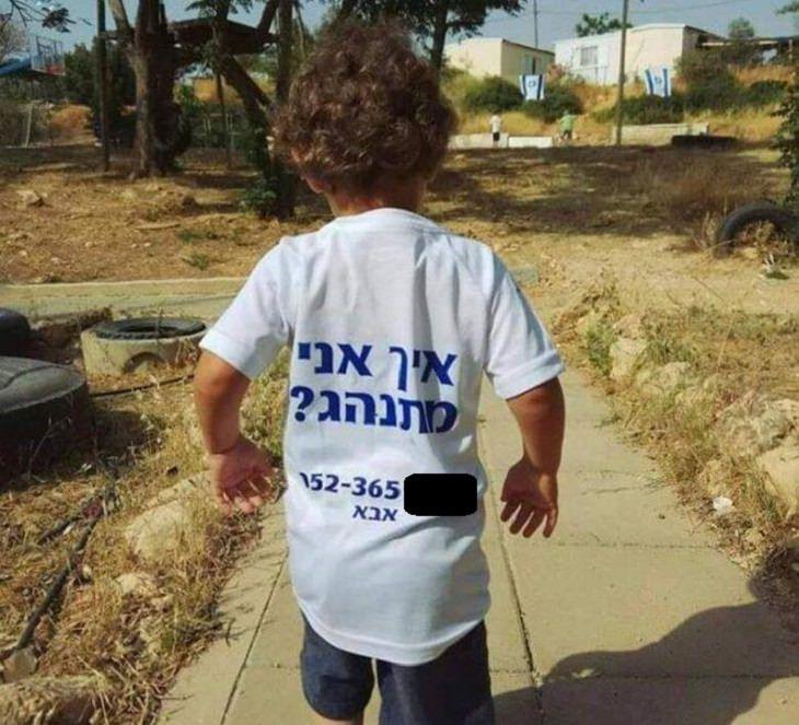 """שלטים מצחיקים: ילד קטן עם חולצה שכתוב עליה """"איך אני מתנהג?"""""""