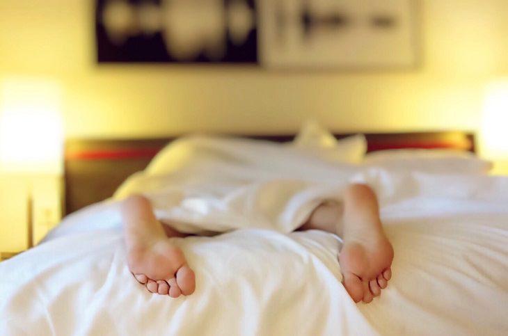 שיטות להתגבר על נדודי שינה: אדם שוכב על מיטה ושתי כפות רגליו יוצאות מחוץ לשמיכה