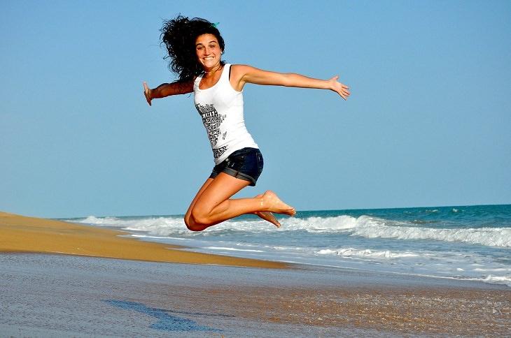 המדריך השלם למגנזיום: בחורה מחויכת קופצת על חוף הים