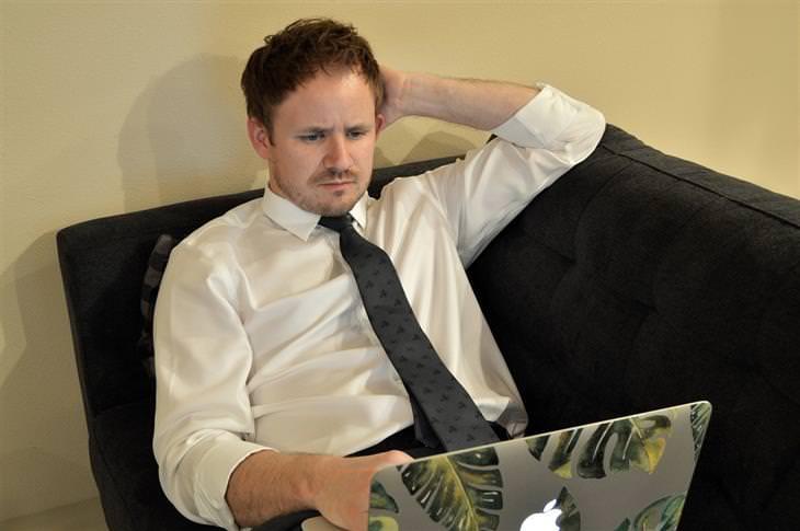 טיפים לעבודה בזום ובמייל: איש עם עניבה שוכב על ספה מול מחשב נייד