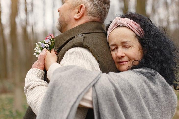 סימנים לכך שמישהו מחבב אתכם: אישה מחבקת איש מאחור ביער