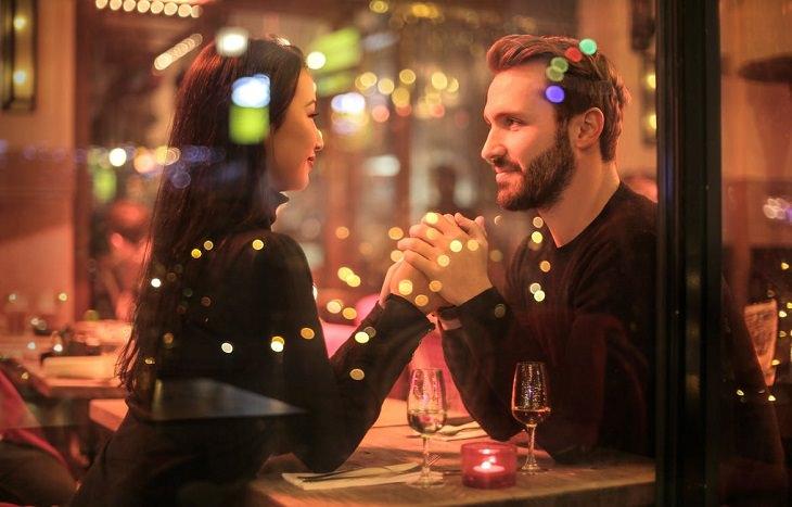 סימנים לכך שמישהו מחבב אתכם: זוג מחזיק ידיים במסעדה