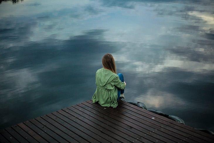 סיבות לעצב: בחורה יושבת על קצה של מזח