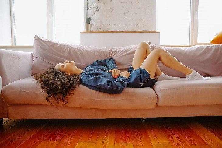 יתרונות בריאותיים של ליצ'י: בחורה שוכבת על ספה ומחזיקה את בטנה