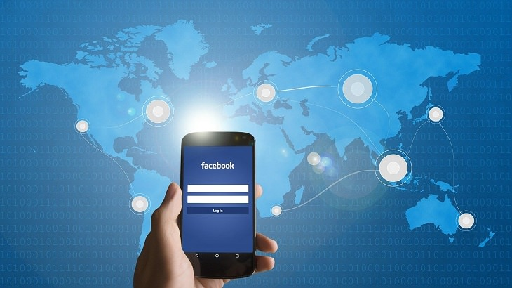פייסבוק רומס: אדם מחזיק טלפון שאפליקציית פייסבוק פתוחה על רקע מפת העולם עם נקודות מחוברות עליה
