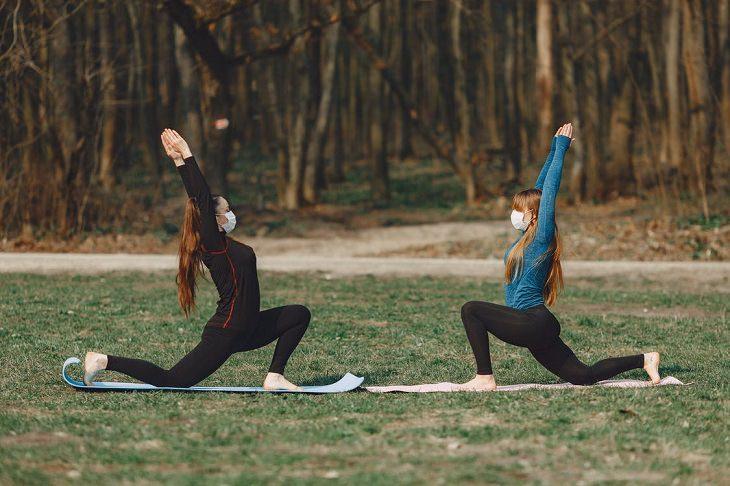 תרגילי לאנג' בהליכה: שתי בחורות מבצעות לאנג' בפארק עם מסכה על הפנים