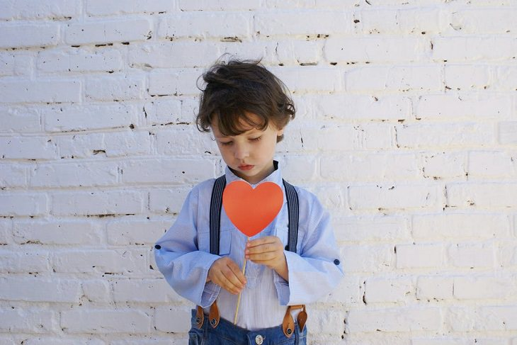 אינטליגנציה רגשית אצל ילדים: ילד עצוב, מחזיק לב מקרטון על מקל