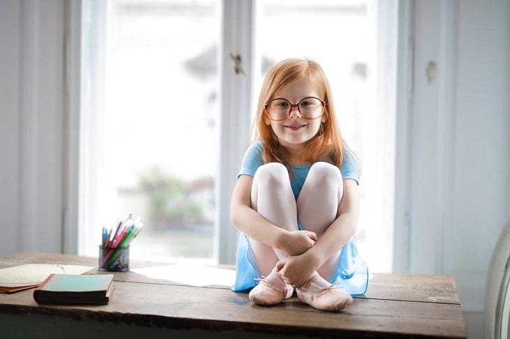 אינטליגנציה רגשית אצל ילדים: ילדה עם משקפיים יושבת על שולחן
