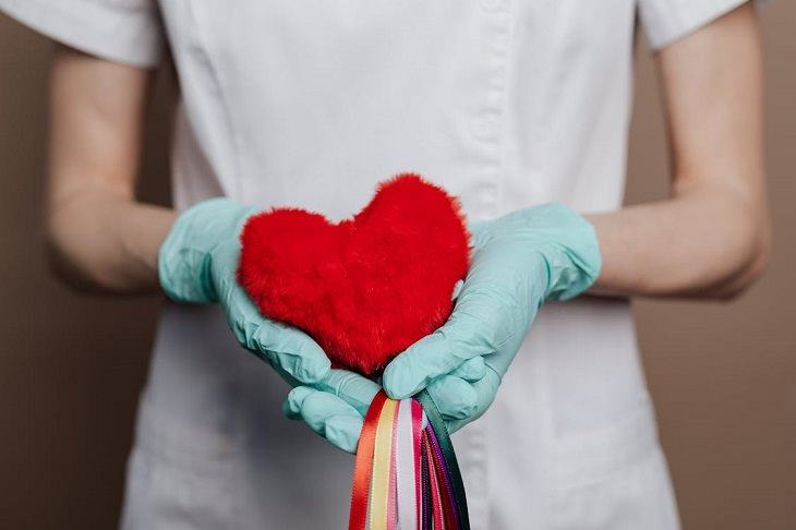 יתרונות בריאותיים של עלי ארוגולה: אחות עם כפפות אוחזת בכרית קטנה של לב, שממנה יוצאים סרטים צבעוניים