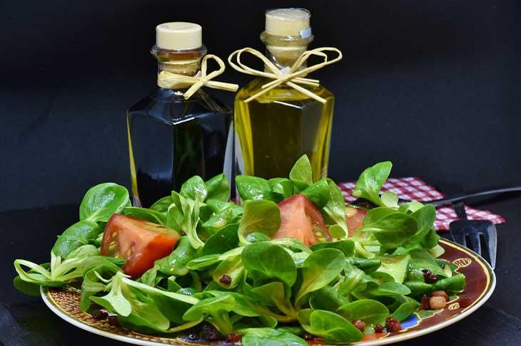 יתרונות בריאותיים של עלי ארוגולה: צלחת עם עלי ארוגולה ועגבניות, ומאחוריה שני בקבוקוני שמן