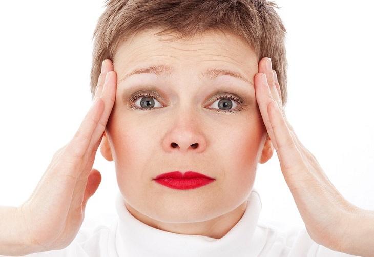 תוספי תזונה נגד בעיות נפוצות: אישה מחזיקה בידיה בצידי ראשה