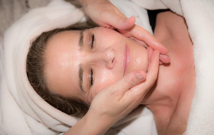 טיפים למניעת צניחת עור הפנים: אישה שעושים לה עיסוי פנים בשכיבה