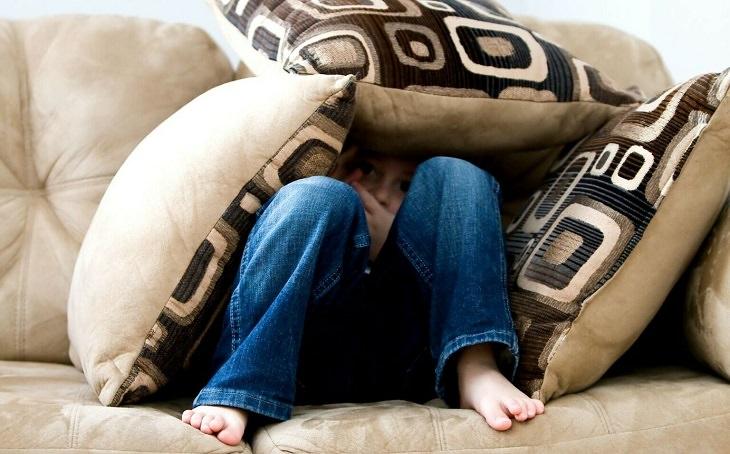 התמודדות נכונה עם ויכוחים בין הורים לילדים קטנים: ילד מתחבא מתחת לכריות ספה