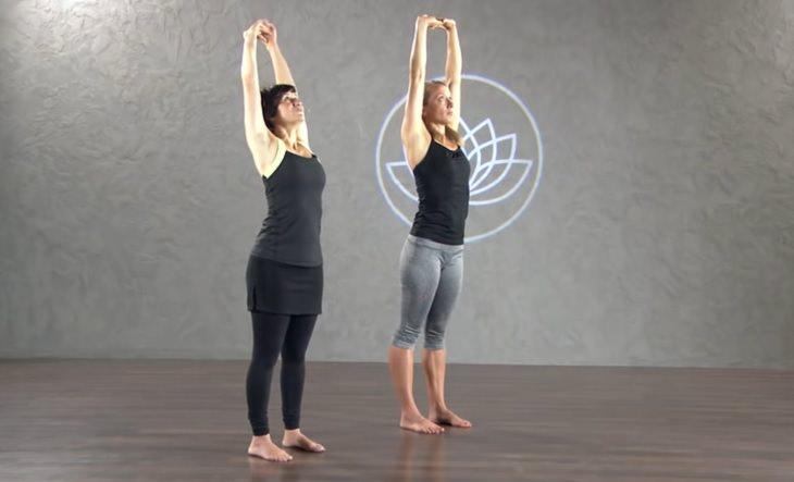 תרגילי כושר לחיזוק הכתפיים: שתי נשים מבצעות מתיחה למעלה