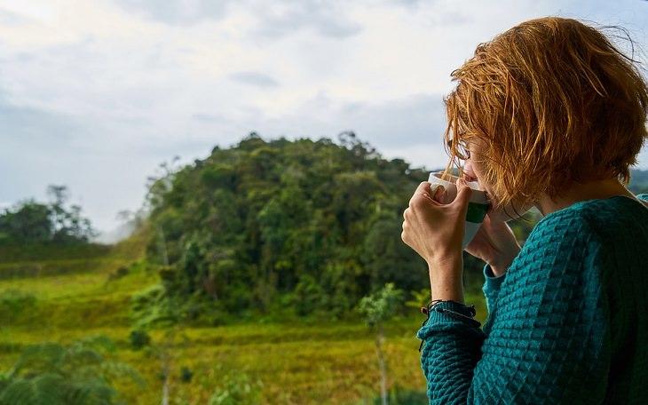 משקה בריאות הודי: אישה שותה מכוס מול חלקה ירוקה