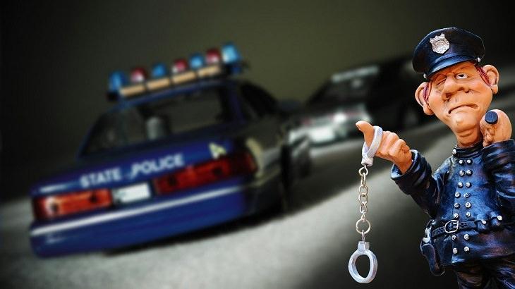 בדיחה על נהג ושוטר: בובה של שוטר מחזיק אזיקים ואלה על רקע מכונית