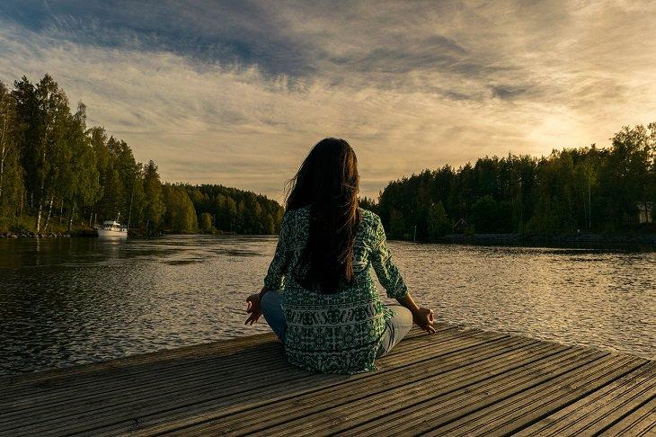 טכניקות קלות להפגת מתחים: אישה יושבת מול נוף אגם ועושה יוגה