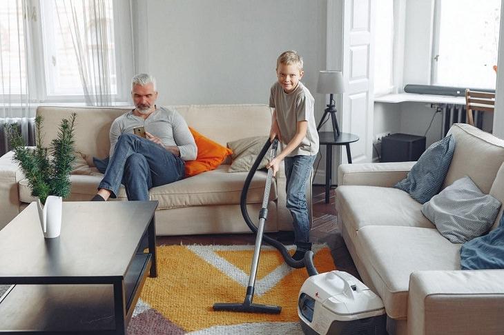 פעילויות חינוכיות לקיץ: אבא יושב על הספה ובן ששואב אבק משטיח