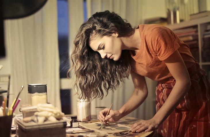 טיפים לשמירה על יציבה נכונה: בחורה עומדת כפוף ומציירת