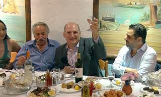 """אוסף כתבות על יוון: גברים בארוחה, שאחד מהם מרים """"לחיים"""""""