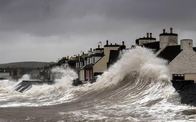 גלי ים מתנפצים על בתי מגורים