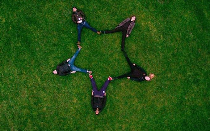אנשים שוכבים על הדשא ויוצרים עם גופם צורת כוכב