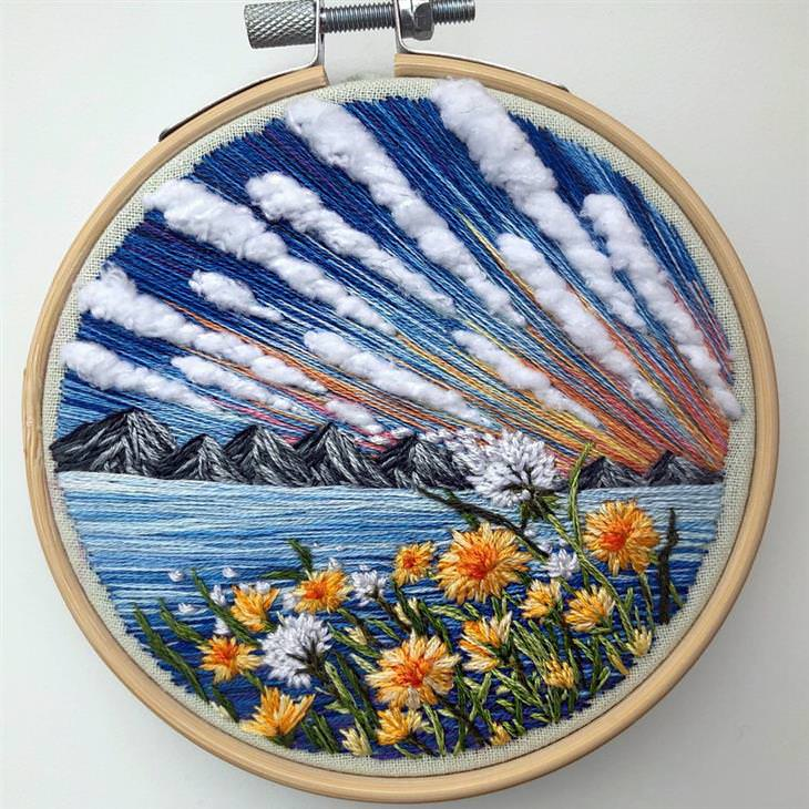 עבודות רקמה של נוף: חוף על רקע הרים ועננים בשמים