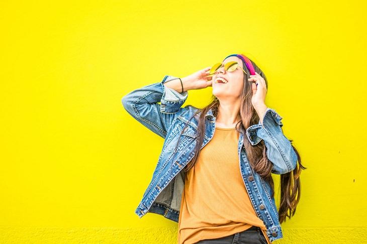 דופמין: בחורה מחייכת ומסתכלת מעלה, על רקע צהוב