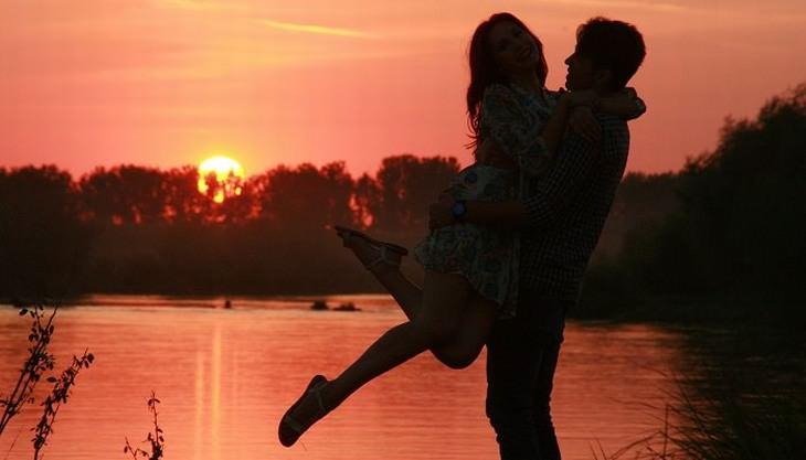 האמת על זוגיות: גבר מחזיק אישה בשעת שקיעה מול אגם