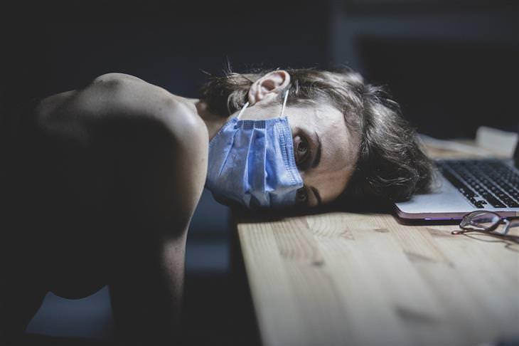 תשישות משבר: אישה עם מסכה משכיבה את ראשה על שולחן