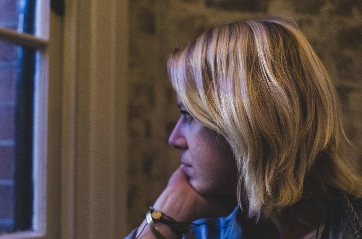 דרכים להפסיק לדאוג: אישה מביטה מהחלון וחושבת