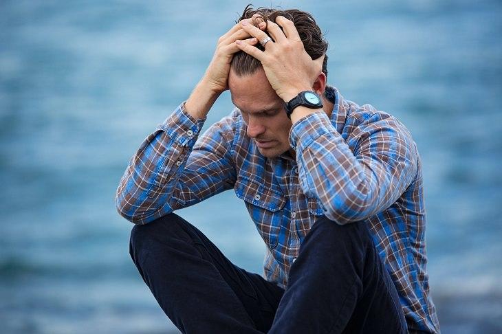דרכים להפסיק לדאוג: בחור יושב על מזח ומחזיק את ראשו בדאגה