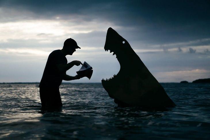 איש שמצלם עצמו עם צלליות בשקיעה: ג'ון מרשל עם דמות כריש