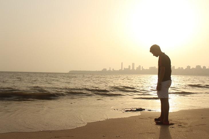 עצות להתמודדות עם חוסר הערכה: בחור עומד על שפת הים ומסתכל מטה בעצב