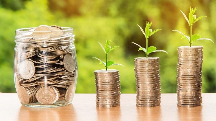 טיפים לילדים על שימוש בכסף לפי גילאים: צנצנת מטבות וערמות מטבות בגבהים שונים
