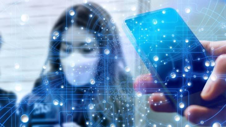 נתוני תחלואת קורונה בישראל: אישה עם מסכת פנים לצד טלפון סלולרי